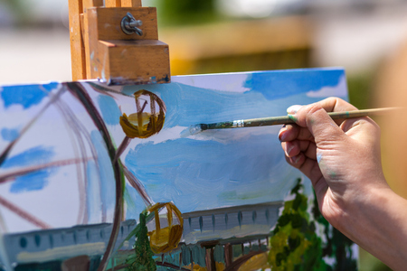 A close-up artist paints on a canvas an urban landscape of a summer with atractions of oil paints