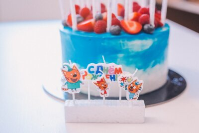 """A close-up of a festive blue and white cake with candles with the inscription """"Birthday"""" and a fruit ornament: strawberries, raspberries, blueberries. Cake for birthday, holiday and anniversary"""