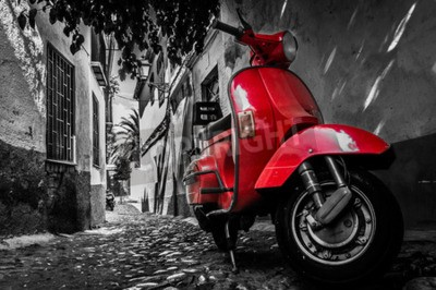 Canvas print A red vespa scooter parked on a paved street