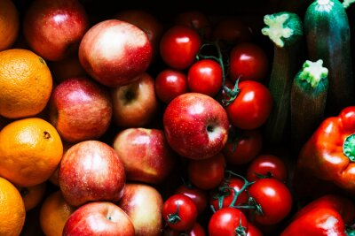 A set of very appetizing raw fruits and vegetables. Set of tomatoes, apples, oranges, peppers and zucchini.