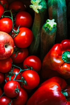 A set of very appetizing raw fruits and vegetables. Set of tomatoes, apples, peppers and zucchini. Red and green fruits and vegetables.