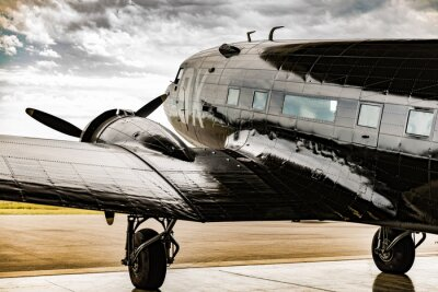 Canvas print A World War II plane looks out from its hanger waiter for the weather to clear