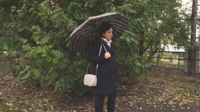A young woman stands with a dark umbrella. Against a green tree. Autumn weather. Leaf litter. Brown. Dark coat and leather boots. The wind blows.