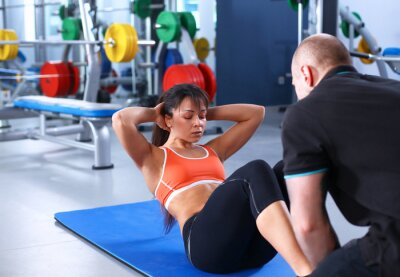 Canvas print A young woman with her coach at the gym