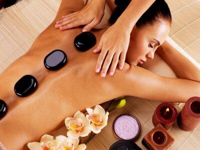 Canvas print Adult woman having hot stone massage in spa salon
