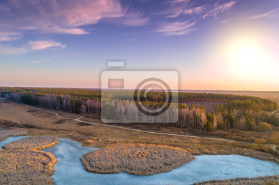 Aerial view of countryside and frozen brook in evening at sunset light. Beautiful nature landscape with cloudy sky.