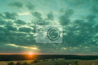 Aerial view of countryside in evening at sunset light. Beautiful nature landscape with cloudy sky