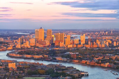 Canvas print Aerial view of east London financial district of Canary Wharf Docklands circled by Thames river, with buildings illuminated by colourful sunset