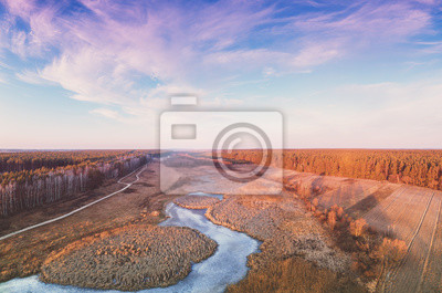 Aerial view of the countryside and frozen brook in the evening at sunset light. Beautiful nature landscape with cloudy sky. Scenic landscape