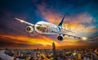 Canvas print Airplane for transportation flying over the night scene city on beautiful sunset background