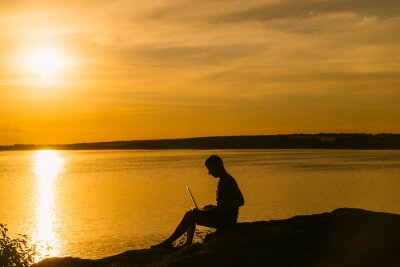 an adult man works at a laptop near the river on the background of a sunset in the summer. Wonderful evening landscape.