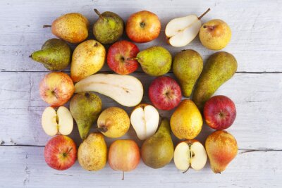 Canvas print apples and pears whole and halved shot from above on white wooden boards