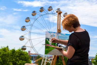 Arrtist  young woman paints on a canvas an urban landscape of a summer  with atractions of oil paints in city park