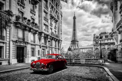 Canvas print Artistic Paris, France. Eiffel Tower seen from the street with red retro limousine car.