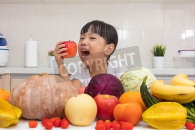Asian Chinese little girl eating apple infront fruit and vegetable in the kitchen at home.
