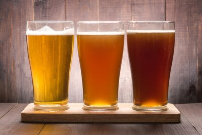 Canvas print Assortment of beer glasses on a wooden table