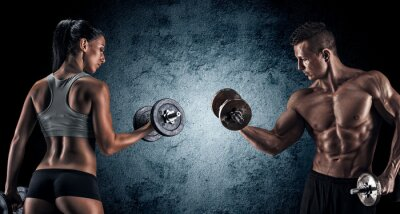 Canvas print Athletic man and woman with a dumbells.