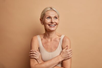 Canvas print Attractive positive wrinkled fifty years old woman looks gladfully above keeps arms foded has well cared complexion healthy skin white teeth isolated over brown background. Beauty and age concept