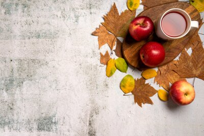 Autumn breakfast. Red apples, cup of tea, leaves, on  gray concrete background. Flat lay.