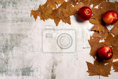 Autumn composition. Red apples, autumn leaves, on  gray concrete background. Flat lay.