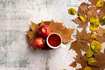 Autumn composition. Red apples, cup of tea, leaves, on  gray concrete background. Flat lay.