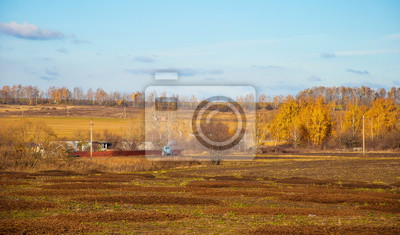 Autumn rural landscape with field and tractor