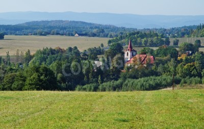Autumn rural landscape with village church, in the background of wooded mountains, view from above