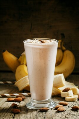 Canvas print Banana smoothie with milk, ground almonds in a large cup on the