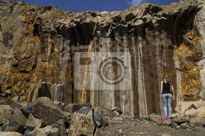 Canvas print Basalt for building. Basalt career. Basalt pillars. Stone excavation. Heavy industry. A girl examines basalt pillars