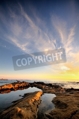 Beatiful sunset at sea with rocks, clouds and blue sky