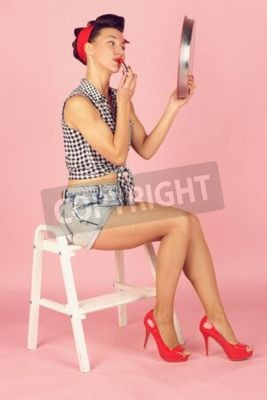 Beautiful brunette woman paints lips with lipstick, looking in a mirror, pin-up style on pink background