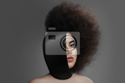 Beautiful brunette  Woman with Clean  Skin. Professional Makeup.  Fashion shiny highlighter on skin, sexy gloss lips  hair smooth and laid his neck the other half curly stranded on  gray background