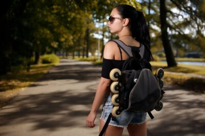 Canvas print Beautiful girl brunette with backpack behind back in which roller skates