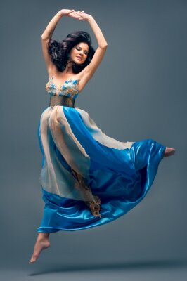 Canvas print beautiful girl floating in mid-air, blue silk dress