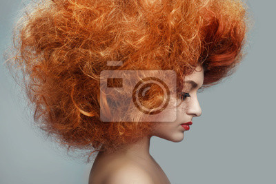 Beautiful   redhead Woman with Clean Fresh Skin. Close up Portrait.  Girl Face. Perfect Skin. Professional Makeup.  shiny highlighter on skin, sexy gloss lips and  curly hair  on  a gray background