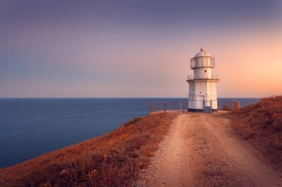 Canvas print Beautiful white lighthouse on the ocean coastline at sunset. Lan