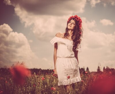 Canvas print Beautiful young brunette girl in poppy filed