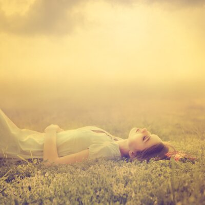 Canvas print beautiful young girl dreams of lying on a magic meadow in spring