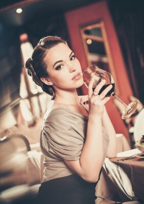 Canvas print Beautiful young girl with glass of red winein a restaurant