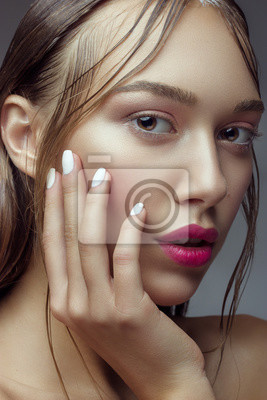 Beautiful Young Woman with Clean Fresh Skin. Close up Portrait. Fashion Model Girl Face. Perfect Skin. Professional Makeup. Fashion shiny highlighter on skin, sexy gloss lips perfect manicure.