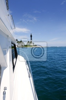 Boat side view and Florida Lighthouse blue sea