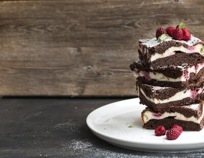 Canvas print Brownies-cheesecake tower with raspberries on white plate