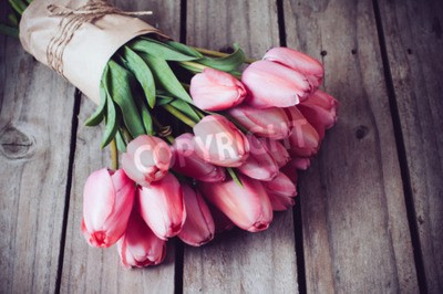 Canvas print Bunch of fresh spring pink tulips on old vintage wooden board, copy space