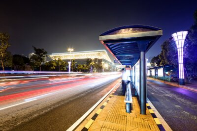 Canvas print bus station next to a road at night