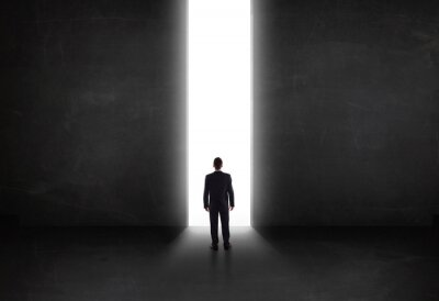 Canvas print Business person looking at wall with light tunnel opening