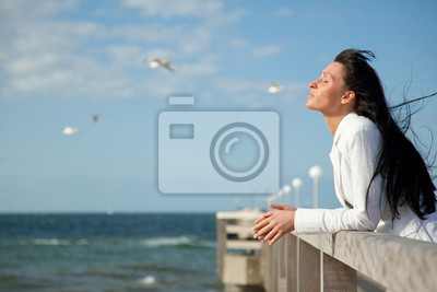 businesswoman on the shore ridge looks into the distance at the lake