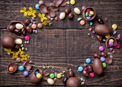 Canvas print Chocolate easter eggs and sweets on wooden background