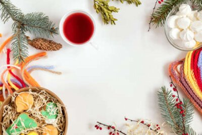 Christmas and New Year composition. Christmas cookies, fir tree and boxwood  branches, cup of hot tea, checkered scarf. Flat lay on white background, top view