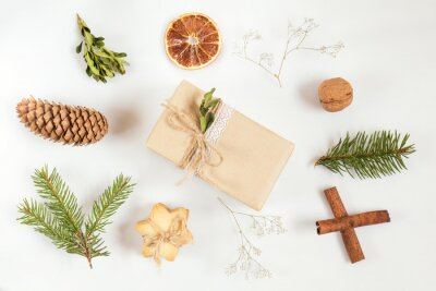 Christmas and New Year composition. Christmas gift, fir tree and buxus boxwood  branches, dry tangerine, nut, cone, cookie, cinnamon and gypsophila flowers. Flat lay on white background, top view