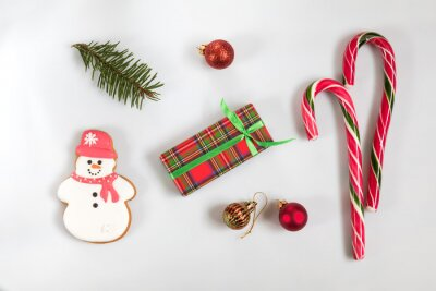 Christmas and New Year composition. Christmas gift, fir tree branches, candy cane, gingerbread snowman. Flat lay on white background, top view